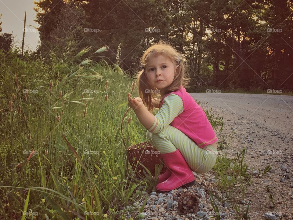 Girl crouching near grass with basket in hand