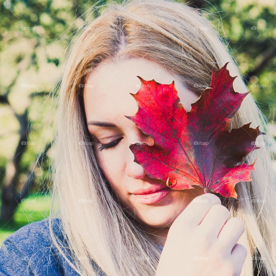 Blonde woman holding red maple leaf