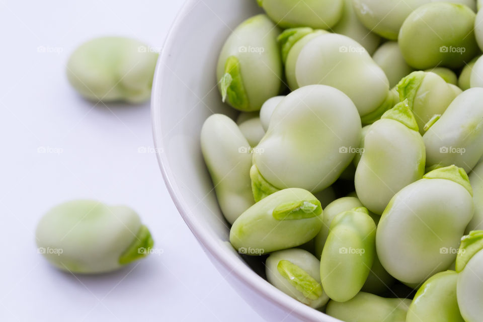 A bowl full of fresh broad beans on a white background.