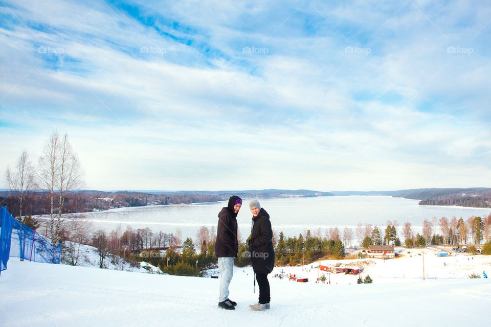 Two friends on top of a snowy hill