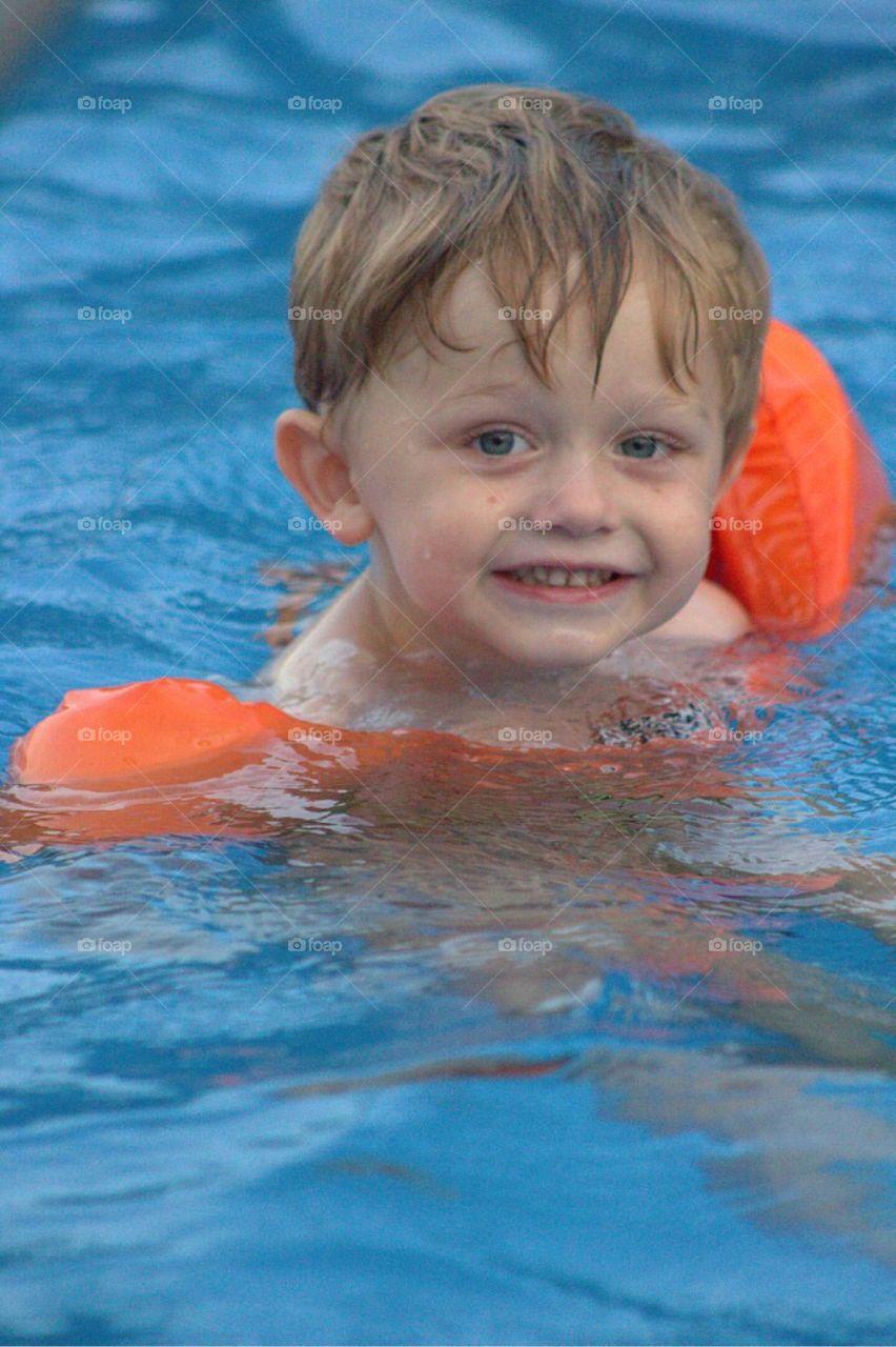 Sweet litter toddler boy, happily swimming along.