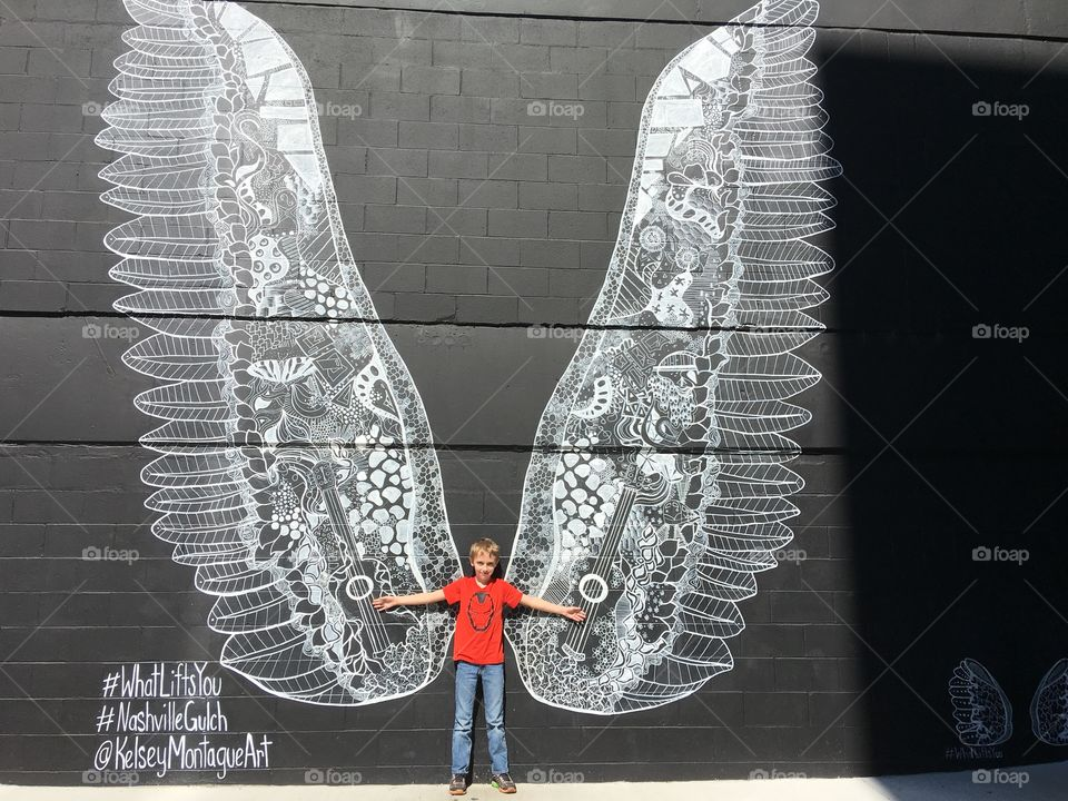 Boy leaning against big white wings on wall
