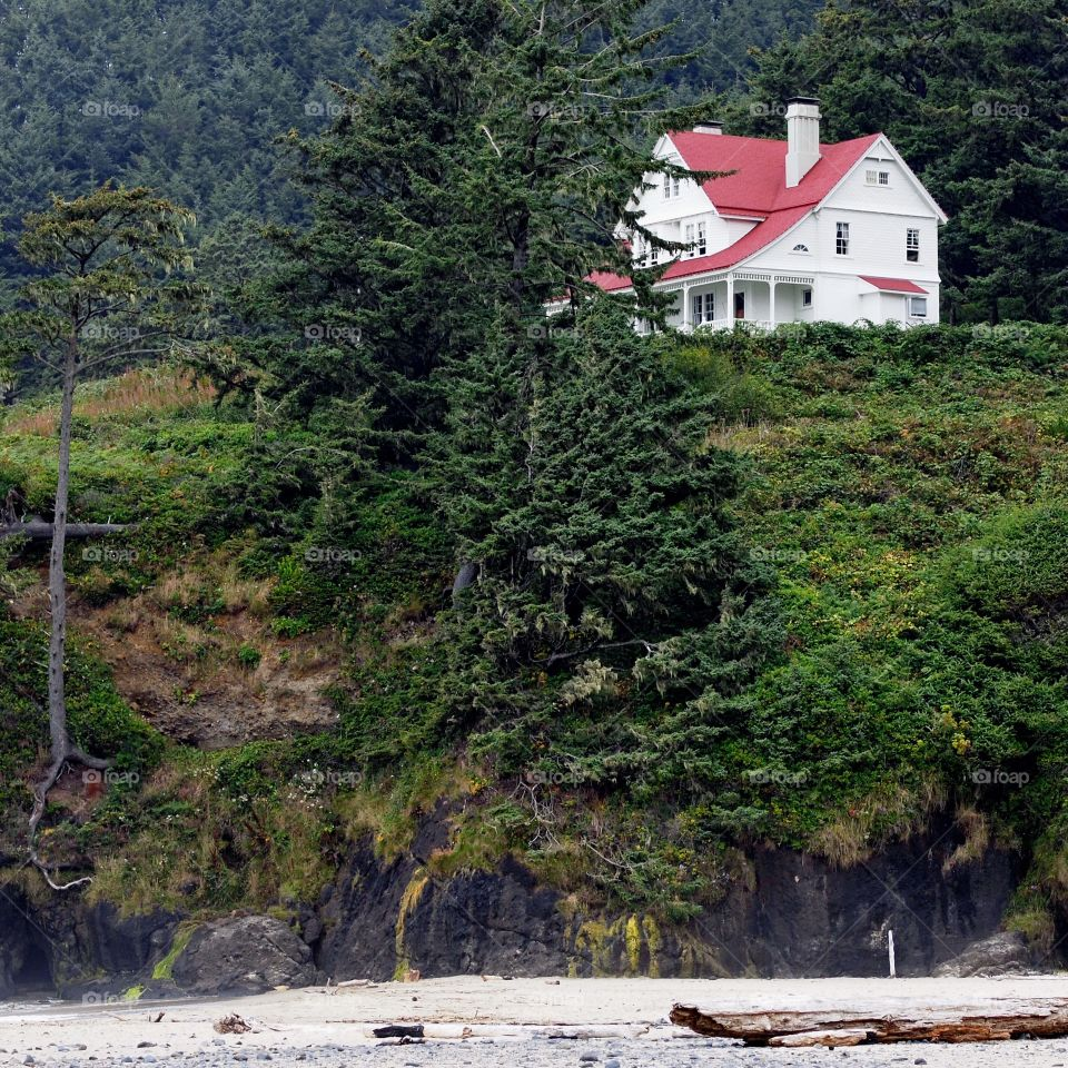 A big two story White House with red roof perched on a cliff in the hills above the Pacific Ocean in the Central Oregon Coast on a fall day.