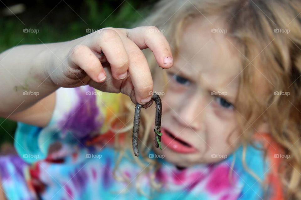 Close-up of a girl holding earthworm