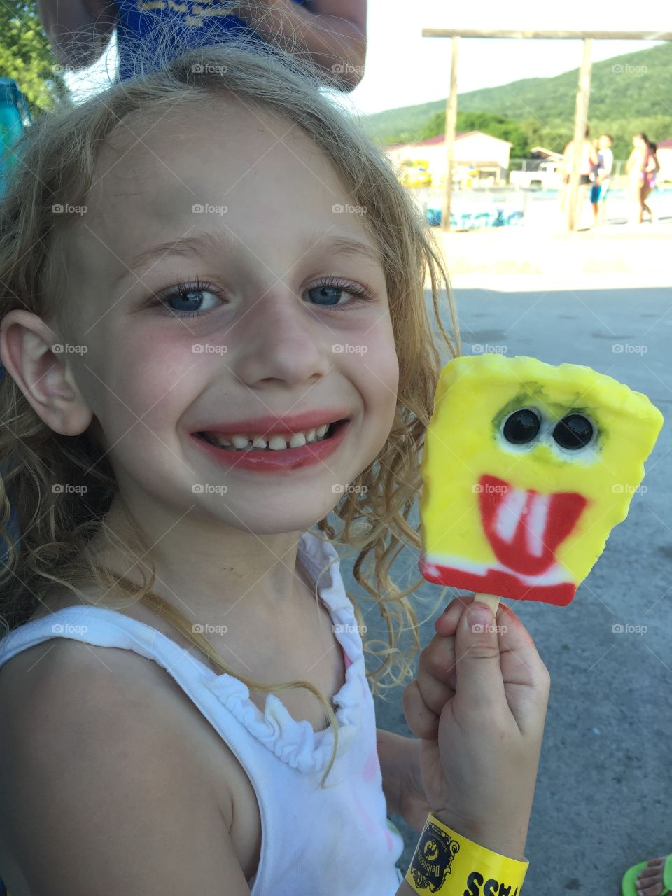 Little girl holding popsicle in hand