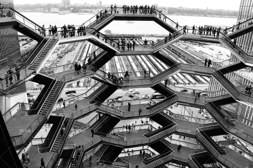 The Vessel, NYC. Modern architecture , black and white .. Staircases connected with platforms to look out .. crowds  watching the beauty of the cityscape from different angles and heights