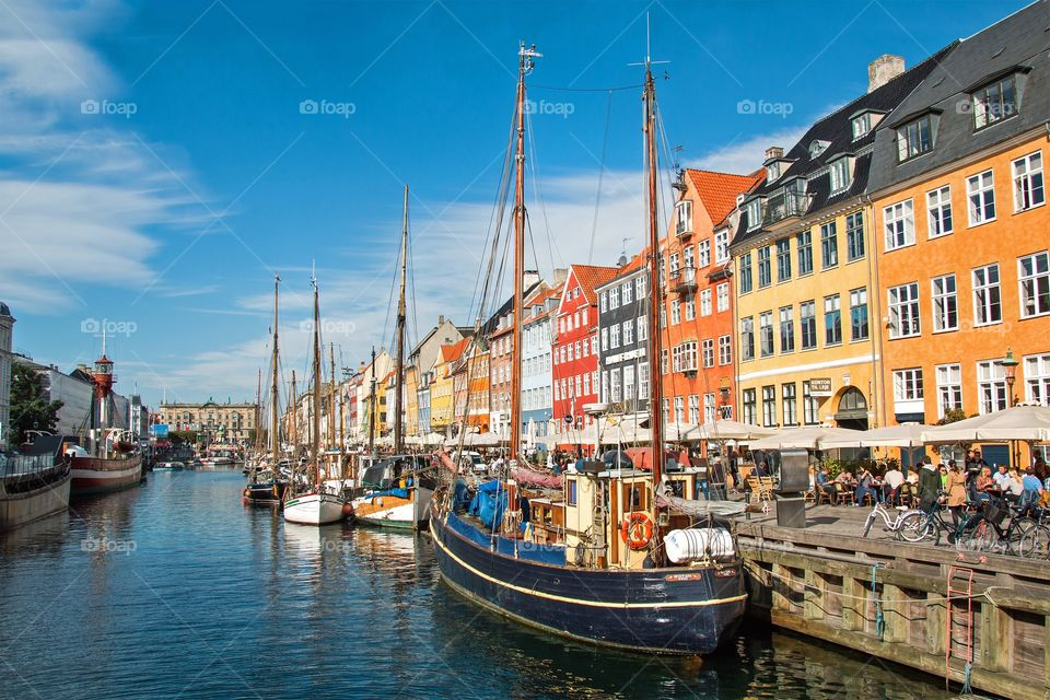 People enjoying Nyhavn in Copenhagen on a sunny day in october