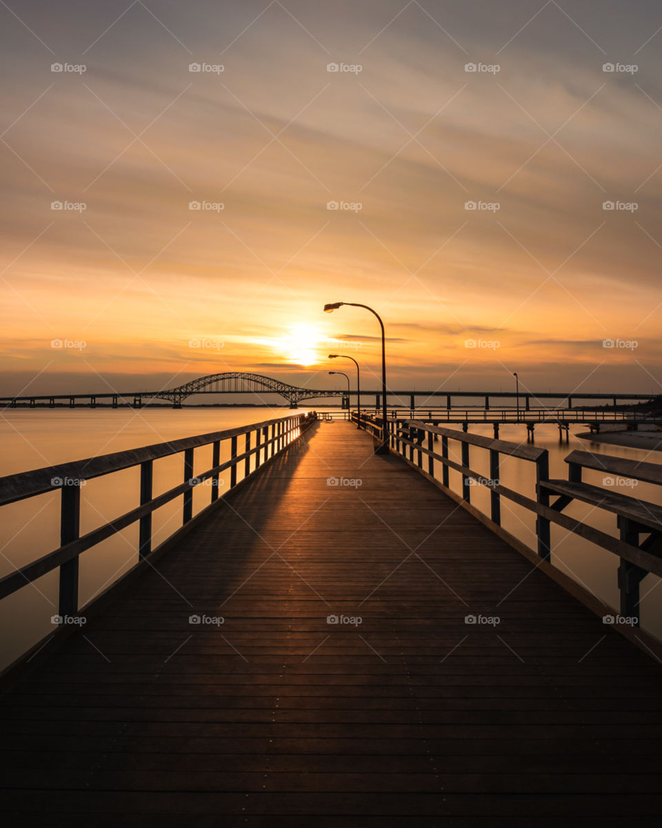 Wooden fishing pier leading out into the sunsets orange sunset colors reflecting on the water and the boardwalk.
