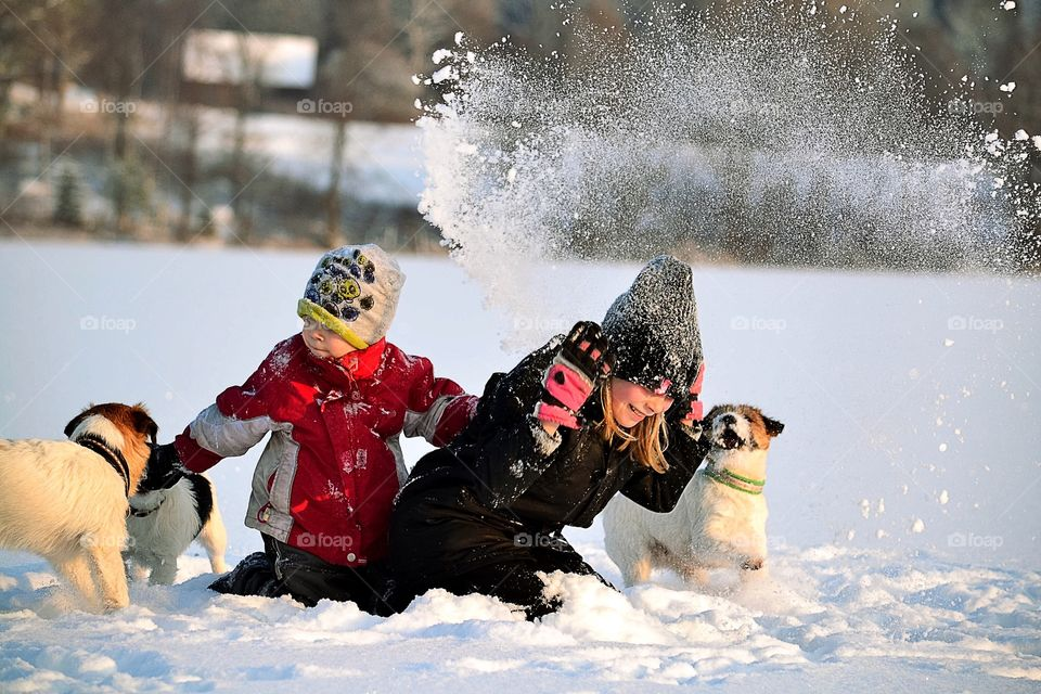 Children's playing in snow with dog