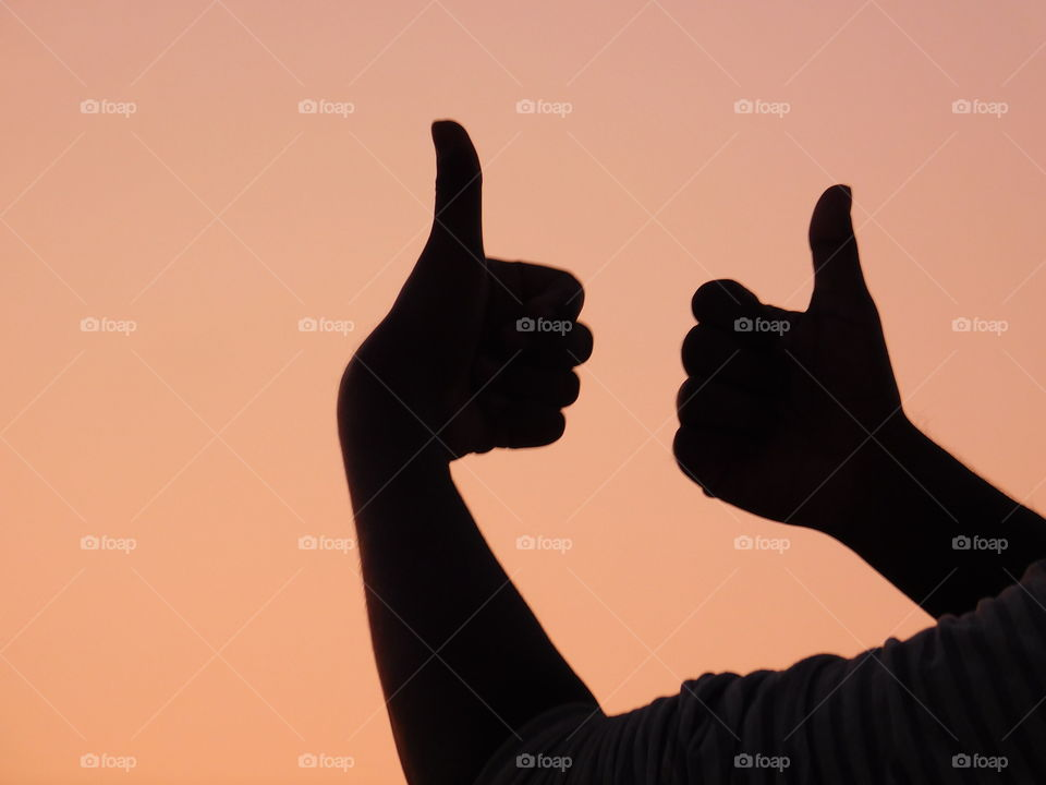 Thumbs-up or All the best silhouette image with sunset light background