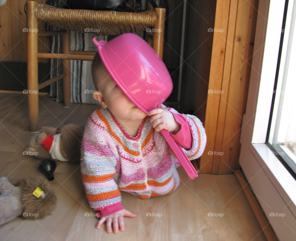 Happy baby girl plays with a pot