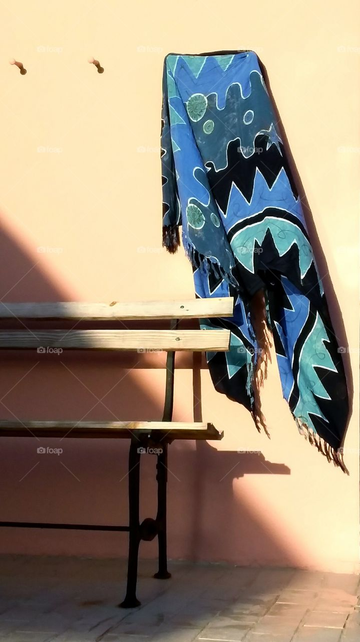 Blue serape blowing in the wind above an antique park bench