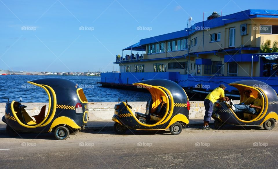Three tricycle Taxis (Cocotaxi) and their unidentified drivers by walls of Havana harbor in Havana, Cuba on 26 December 2013.
