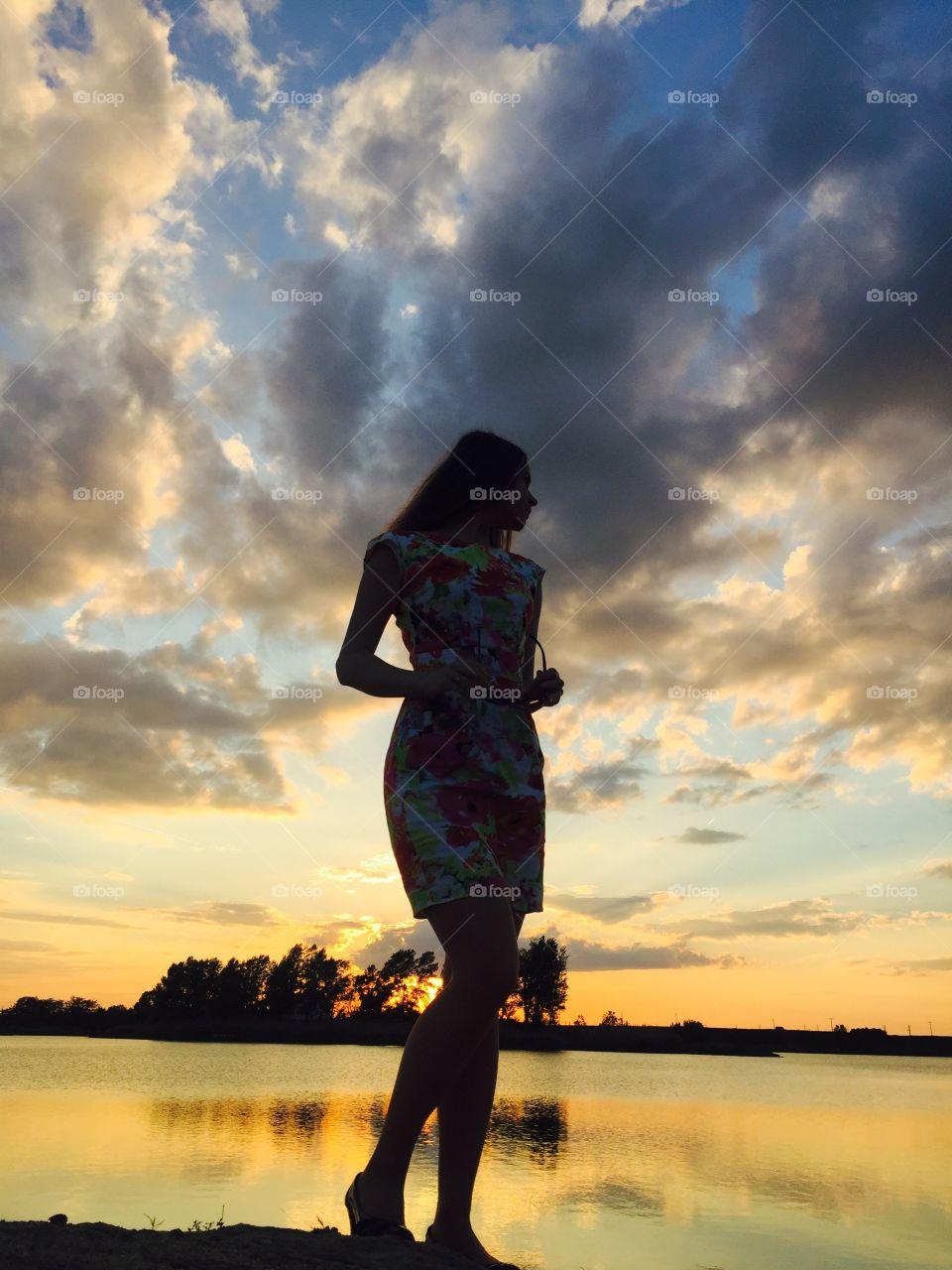 Woman posing near lake during sunset
