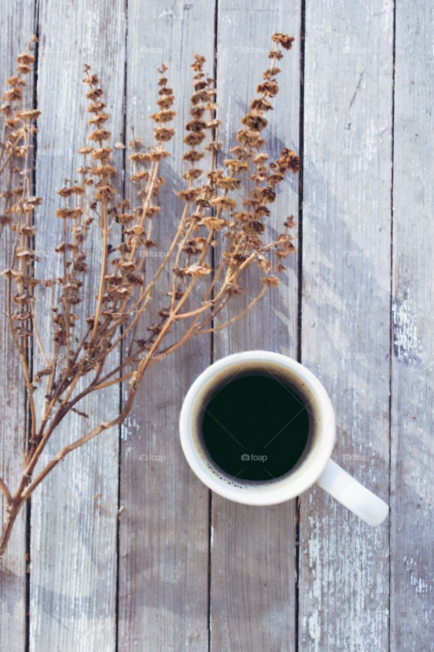 Flat lay of coffee in a white mug next to a dried brown plant on a weathered wooden surface