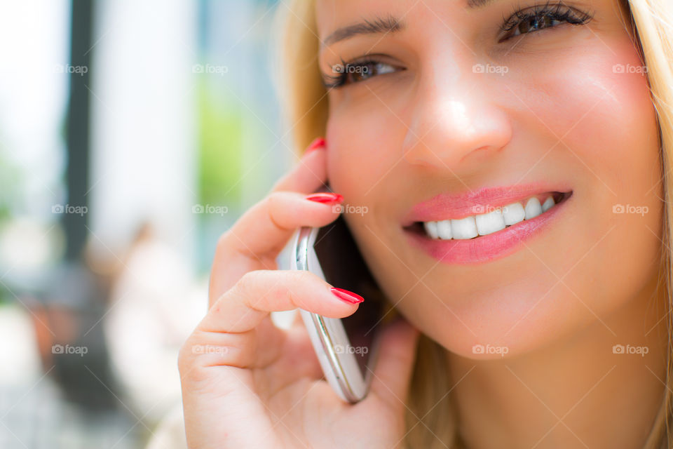 Close-up of a woman talking over mobile phone