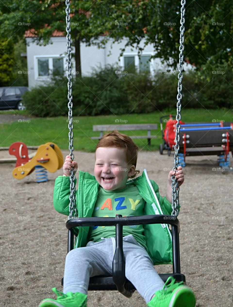 Boy hanging on a swing