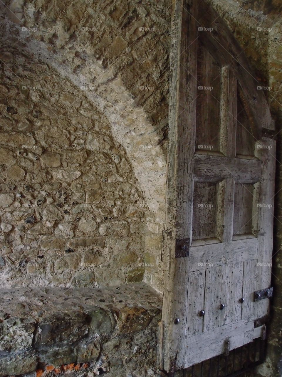 A worn wooden door in a corridor attached to an old stone building in Dover England.